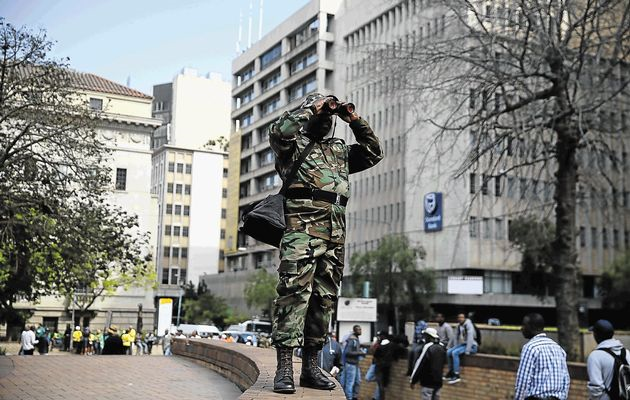 An Umkhonto we Sizwe Military Veterans' Association member scans the surrounds with binoculars near Luthuli House in downtown Johannesburg. The #OccupyLuthuliHouse movement staged a small protest on Monday morning, and called for the resignation of both ANC president Jacob Zuma and his NEC