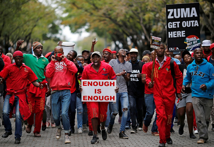 FILE PHOTO: Protesters hold placards as they march to protest against President Jacob Zuma in Pretoria, South Africa, April 12 ,2017. REUTERS/Siphiwe Sibeko/File Photo