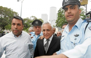 Former Israeli President Moshe Katsav is escorted by police as he leaves the courtroom after being found guilty of rape in Tel Aviv, Israel in 2010