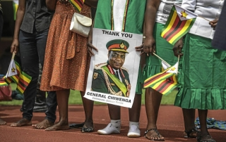 "Wait and see... Supporters hold posters of Zimbabwe Army Chief of Staff General Constantino Chiwenga during newly sworn-in President Inauguration ceremony at the National Sport Stadium in Harare, on November 24, 2017. Zimbabwe's newly sworn-in President Emmerson Mnangagwa vowed during his inauguration speech on November 24 to protect foreign investments in the country as he sought to lay out his economic credentials. ""In this global world no nation is, can, or need be an island. All foreign investments will be safe in Zimbabwe,"" he told a crowd of tens of thousands at his inauguration ceremony. / AFP PHOTO / MUJAHID SAFODIEN"